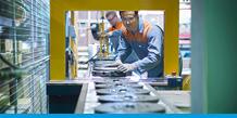 Workers in a U.S. factory operate a machine