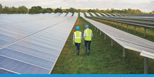Workers walk through a solar panel farm