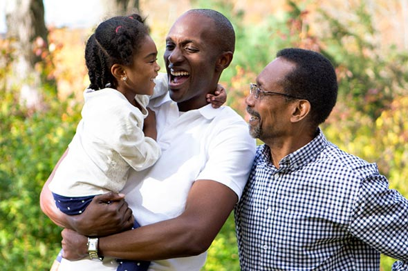 A grandfather, father and young daughter in the park. The father is holding his young daughter as they laugh.